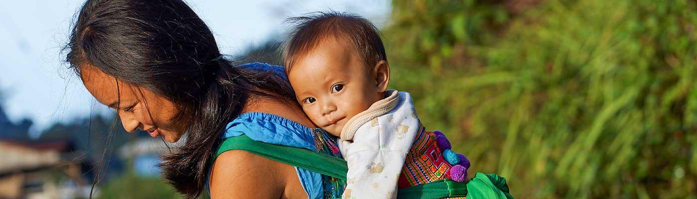 Laotische Mutter mit Kind im Tragetuch